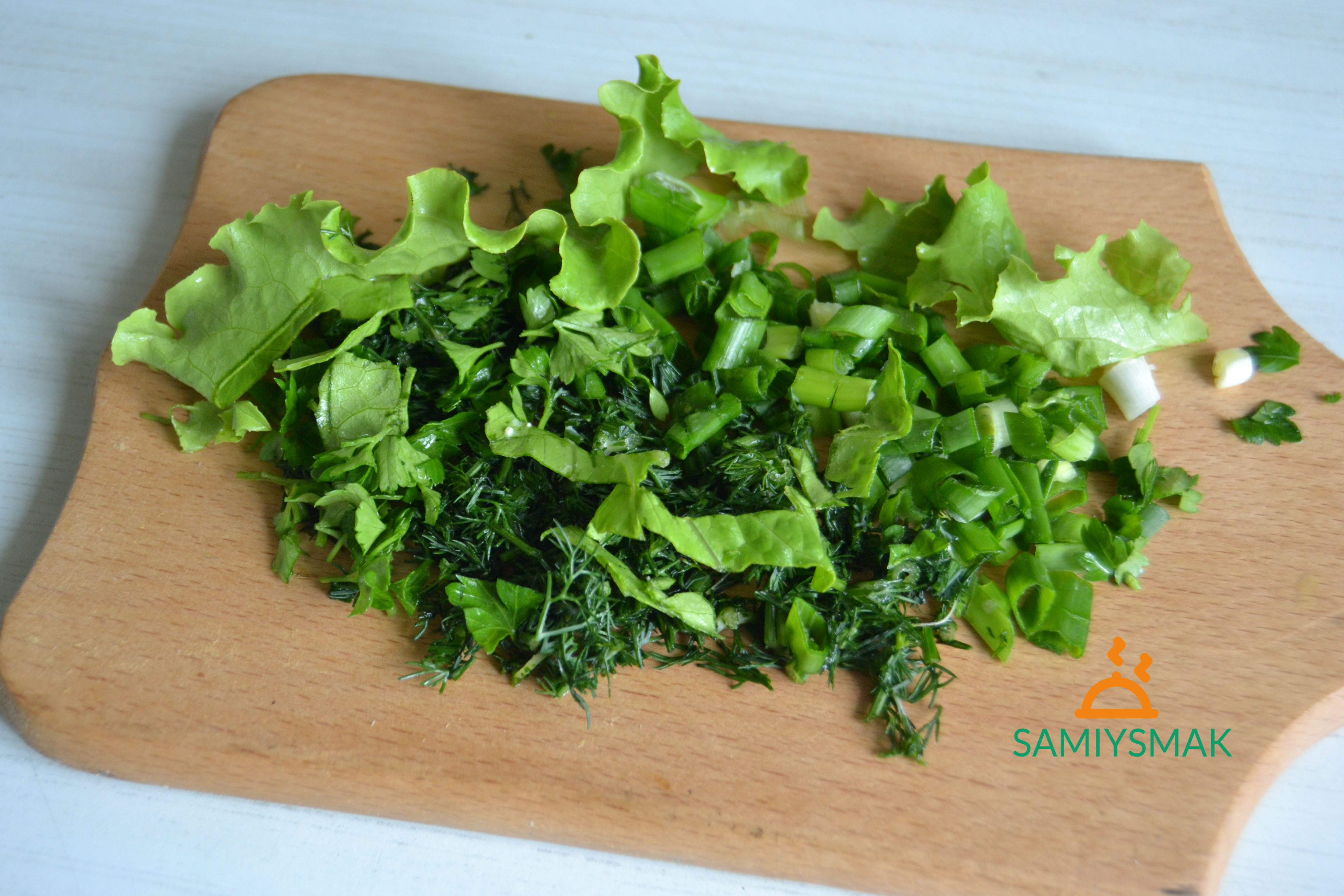 Нарезка свежей зелени на доске
